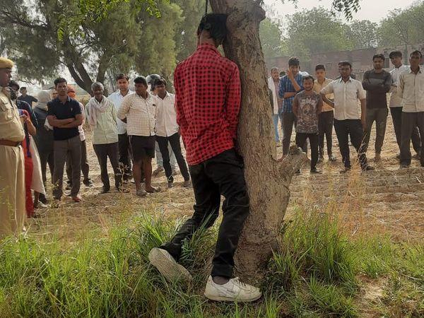चिकसाना क्षेत्र के गांव केवल नगला स्थित राजकीय स्कूल के पीछे नीम के पेड़ से लटकता अस्पतालकर्मी बच्चू सिंह जाटव का शव। - Dainik Bhaskar