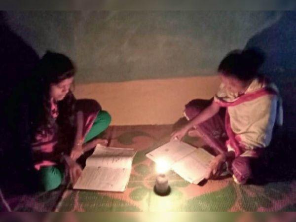 बिजली समस्या के चलते चिमनी की रोशनी में पढ़ाई करते मालगांव के छात्र। - Dainik Bhaskar