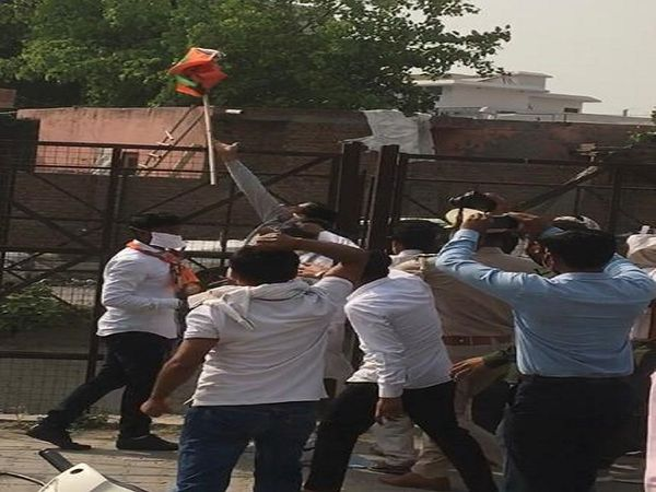 भाजपा के झंडे को नाले में फेंकता किसान।