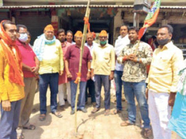 पार्टी कार्यालय में झंडा फहराते बीजेपी कार्यकर्ता। - Dainik Bhaskar