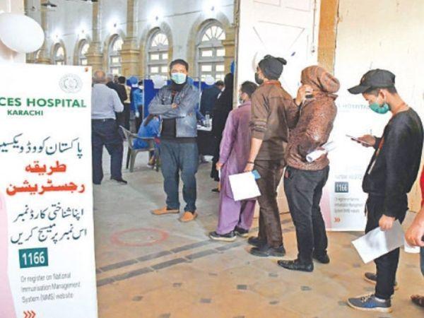 फोटो पाकिस्तान के कराची की है, जहां अस्पतालों में वैक्सीनेशन के लिए लोगों की लंबी कतारें लग रही हैं।