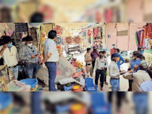 दुकानदारों को मास्क एवं सोशल डिस्टेंसिंग की हिदायत देते अफसर। - Dainik Bhaskar
