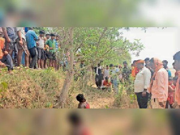 पेड़ से लटकता अज्ञात युवक का शव व ग्रामीणों की भीड़। - Dainik Bhaskar