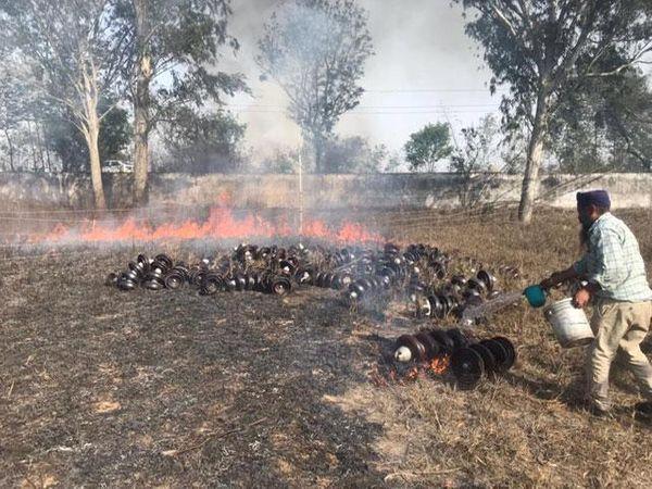 बिजली सप्लाई के सामान को जलने से बचाने के लिए आग बुझाता कर्मचारी।