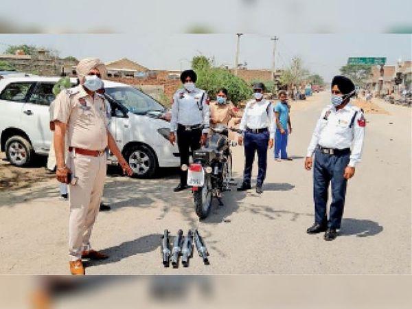 बुलेट मोटरसाइकिलों के साइलेंसर उतारते पुलिस कर्मी। - Dainik Bhaskar