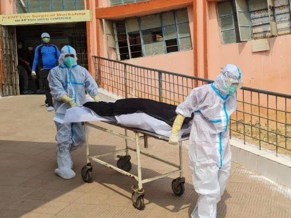 कोरोना से हुई मौत के बाद लाश को बाहर निकालते स्वास्थ्यकर्मी।