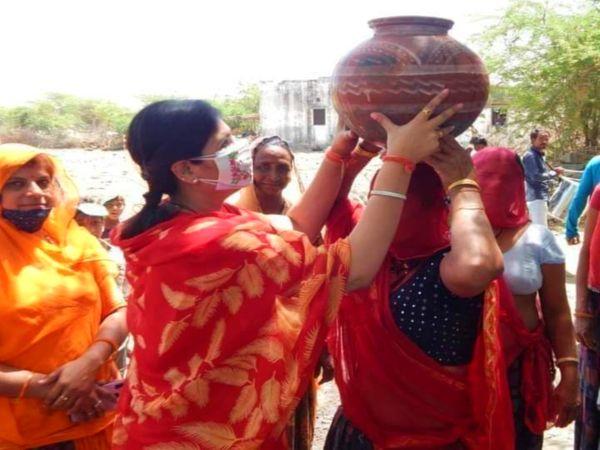 ग्रामीण इलाके में पानी भरने में मदद करती बीजेपी प्रत्याशी दीप्ति माहेश्वरी।