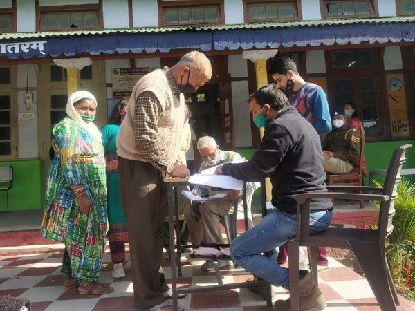 धर्मशाला में नगर निगम चुनाव के लिए वोट डालने पहुंचे लोग और उनकी मदद के लिए तैनात चुनावी अमला। - Dainik Bhaskar
