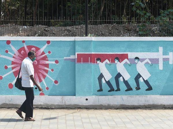 मुंबई में वैक्सीनेशन को लेकर जागरूक करने वाली एक वॉल पेंटिंग के बगल से गुजरता व्यक्ति।