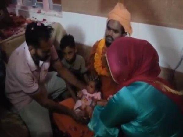 मंदिर के महंत को बच्चा सौंपते अंधविश्वासी मां-बाप। - Dainik Bhaskar