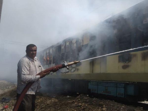 रोहतक रेलवे स्टेशनल पर यार्ड में खड़ी DEMU में लगी आग पर काबू पाने की कोशिश में पानी की बौछार करता दमकल विभाग का कर्मचारी। - Dainik Bhaskar