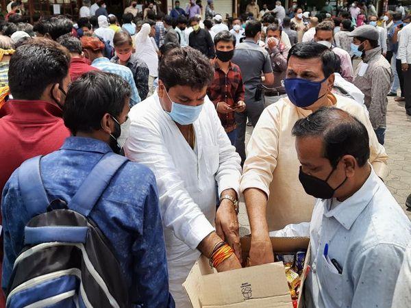 विधायक संजय शुक्ला ने धूप में खड़े लोगों को बिस्किट के पैकेट बांटे।