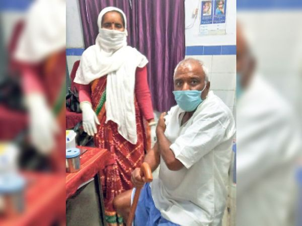 बुजुर्ग को टीका लगाते स्वास्थ्यकर्मी। - Dainik Bhaskar