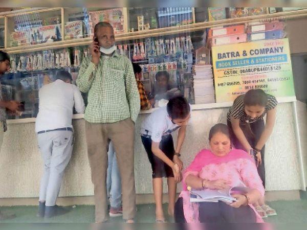 बुक स्टोर पर पाठ्य सामग्री खरीदते हुए अभिभावक। - Dainik Bhaskar