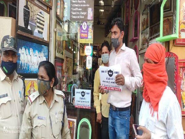 दुकानों में नो मास्क, नो सामान का पोस्टर लगवाती पुलिस।