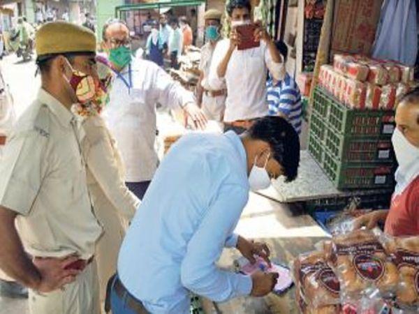 अलवर, बुधवार को शहर में एक दुकानदार का चालान काटती टीम। - Dainik Bhaskar