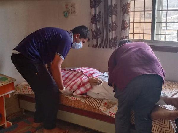 पिता के शव को कवर में पैक करते दोनों बेटे। - Dainik Bhaskar