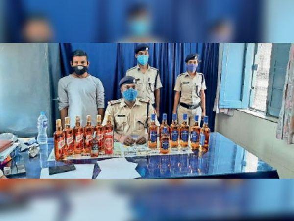 बरामद शराब व गिरफ्तार युवक के साथ आरपीएफ प्रभारी। - Dainik Bhaskar