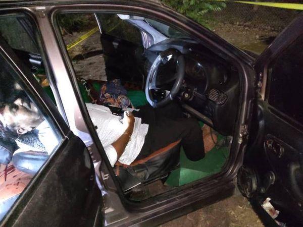 कार की अगली सीट पर पड़ा शव।