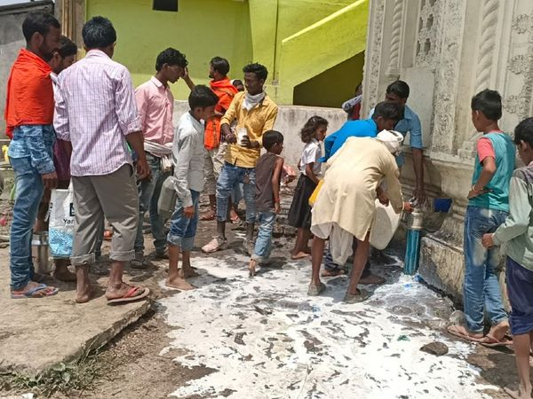 प्रसाद को घर ले जाने के लिए दूध को जमा करते श्रद्धालु।