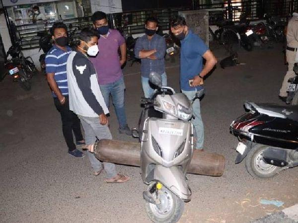 इंदौर में ऑक्सीजन सिलेंडर भरवा कर स्कूटी से लाने की तैयारी करते मरीज के परिजन। यहां 3 हजार गंभीर मरीज भर्ती हैं।