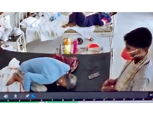 बेड पर तड़प रहे सुरेंद्र शर्मा, पास में उनका बेटा दीपक खड़ा है।