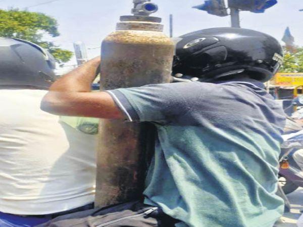 ऑक्सीजन खरीद कर बाइक से ले जाते लोग। - Dainik Bhaskar