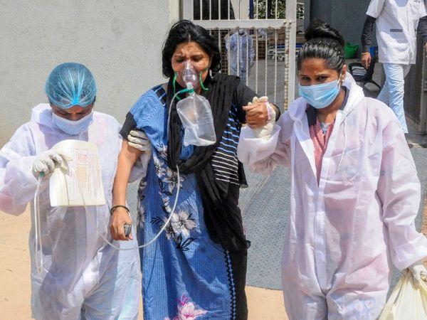 फोटो गुजरात के अहमदाबाद शहर की है। यहां कोविड अस्पताल में स्थिर हालत वाले मरीज को ICU से दूसरे वार्ड में शिफ्ट किया जा रहा है, ताकि गंभीर मरीज को ICU में बेड मिल सके। पूरे गुजरात के अस्पतालों में ICU, ऑक्सीजन और वेंटिलेटर का संकट है। - Dainik Bhaskar