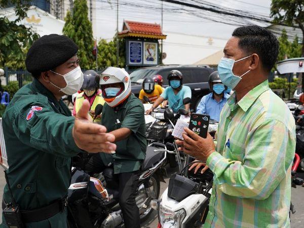 फोटो कंबोडिया की राजधानी प्नॉम पेन में लगे लॉकडाउन की है, जहां पुलिस एक व्यक्ति को रोक रही है और वो जाने के लिए मिन्नतें कर रहा है। - Dainik Bhaskar