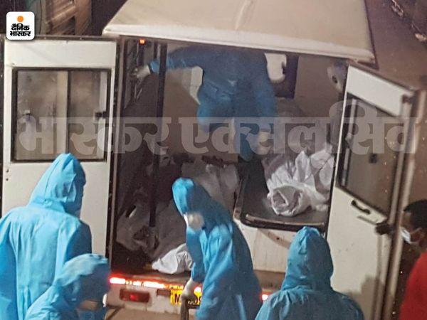 एंबुलेंस में शव ले जाते अस्पतालकर्मी।