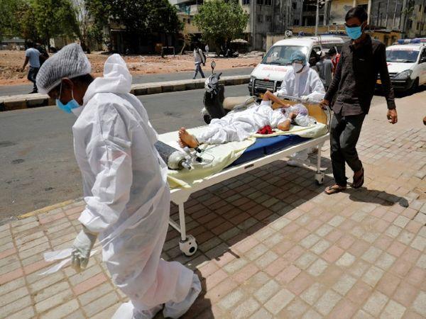 अहमदाबाद के एक अस्पताल के बाहर कोरोना मरीज को बेड सहित ले जाते मेडिकल कर्मचारी। - Dainik Bhaskar