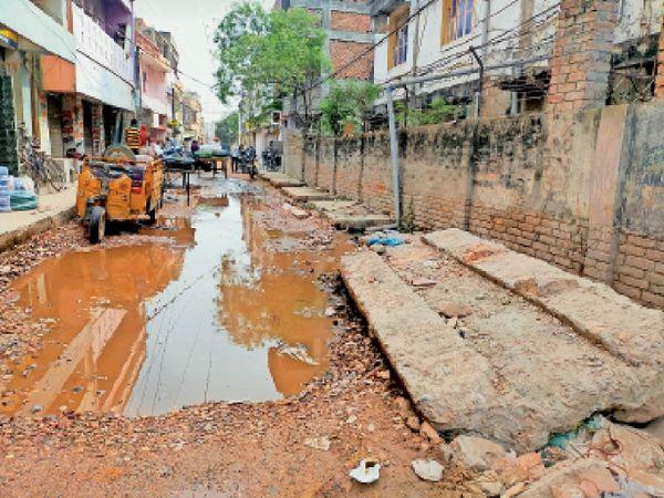पंकज मार्केट रोड में नाला निर्माण के कारण सड़क पर फैला दूषित पानी और कंकर-पत्थर। - Dainik Bhaskar