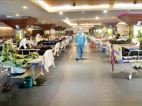 डॉक्टर की निगरानी में नई दिल्ली के बैंक्वेट हॉल में बने अस्पताल में भर्ती मरीज। - Dainik Bhaskar