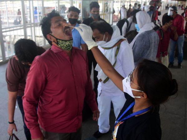 प्रयागराज रेलवे स्टेशन पर सोमवार को प्रवासी मजदूरों का सैंपल कलेक्ट करती हेल्थकेयर वर्कर।