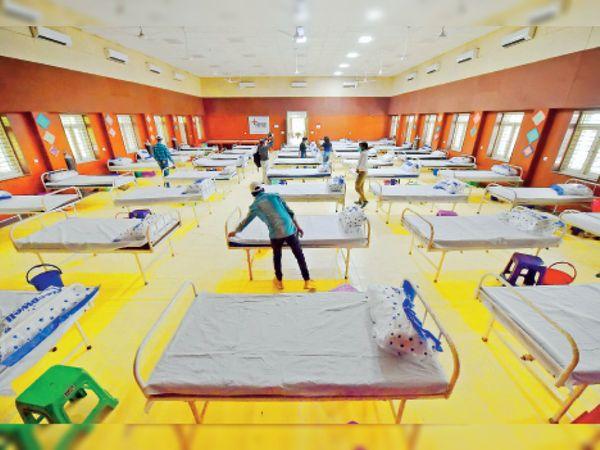 दिल्ली के स्कूल में कोविड केयर रूम तैयारी करते वर्कर। - Dainik Bhaskar