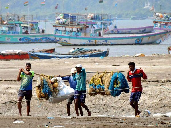 मुंबई में पूर्ण लॉकडाउन की संभावना के बाद अपने जाल को लपेटकर समद्र से बाहर आती मछुआरों की टोली।