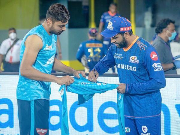 दिल्ली के तेज गेंदबाज आवेश खान को टी-शर्ट पर साइन करके देते हुए रोहित शर्मा।