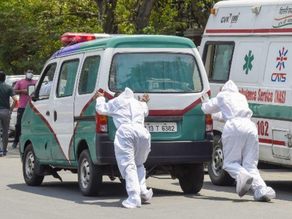 फोटो दिल्ली की है। यहां कोरोना मरीज को अस्पताल ले जा रही एक एंबुलेंस बीच रास्ते में खराब हो गई। स्वास्थ्यकर्मियों को धक्का देकर इसे आगे ले जाना पड़ा।