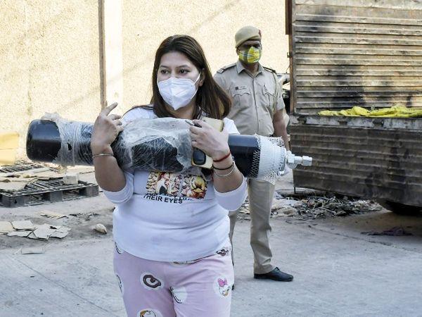 फोटो दिल्ली की है। यहां ऑक्सीजन सिलेंडर के लिए मयूरपुरी में कोविड-19 मरीजों के परिजनों की भीड़ जुट रही है। महिला सिलेंडर उठाकर ले जाते हुए।