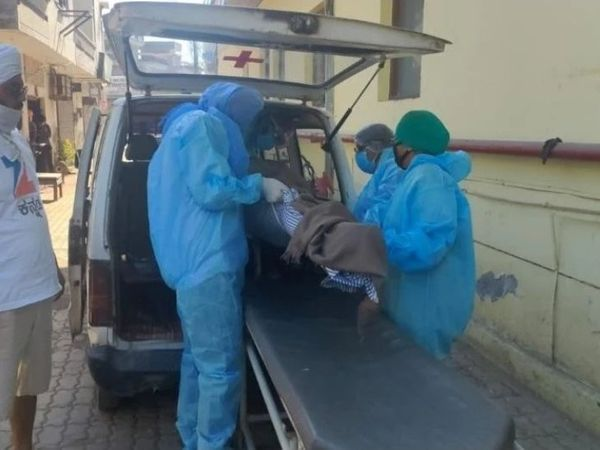 शवों को अंतिम संस्कार के लिए ले जाते अस्पताल कर्मी।