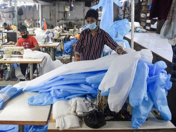 लॉकडाउन के बीच मुंबई में मेडिकल उपकरणों का निर्माण लगातार जारी है। यहां एक फैक्ट्री में PPE किट बनाते कुछ फैक्ट्री वर्कर।