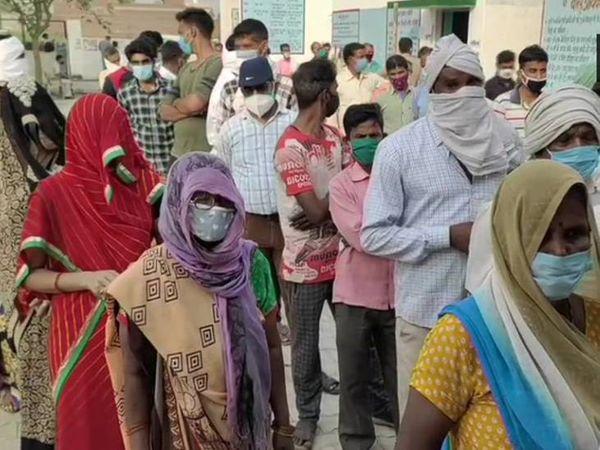 अलीगढ़ के सिंघौली के एक मतदान केंद्र पर मतदाताओं की लगी कतार।