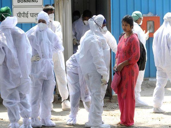 मुंबई के जंबो कोविड सेंटर के बाहर अपनी शिफ्ट से पहले PPE किट पहनकर तैयार होते BMC के स्वास्थ्यकर्मी।