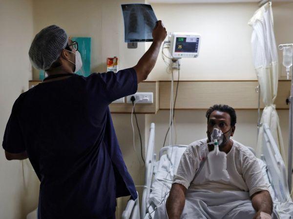 दिल्ली के एक अस्पताल के कोरोना वार्ड में संक्रमित मरीज का एक्स-रे देखते डॉक्टर। - Dainik Bhaskar