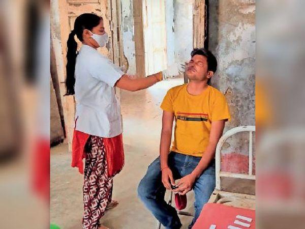 कोरोना जांच के लिए संदिग्ध का सैंपल लेते स्वास्थ्यकर्मी। - Dainik Bhaskar