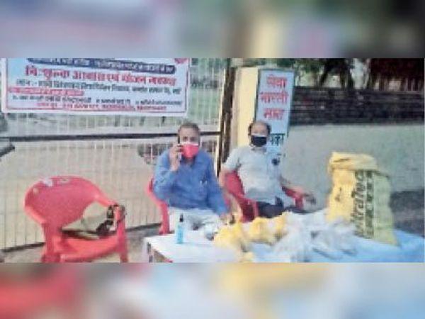 बारां. जिला अस्पताल में भोजन के पैकेट वितरित करते कार्यकर्ता। - Dainik Bhaskar