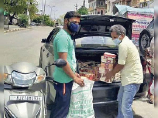 जरूरतमंद लाेगाें काे भाेजन के पैकेज बांटने की सेवा मेें थे विनाेद जैन(पीली शर्ट में)।    -फाइल फोटो - Dainik Bhaskar