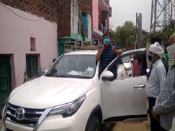 कार पर खड़े होकर लोगों को अनाउंसमेंट कर मास्क लगाने के लिए जागरूक करते हुए मंत्री।