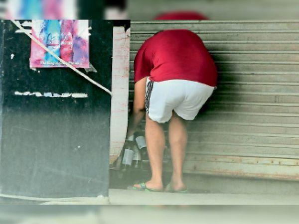 सेक्टर-14 में ठेके से शटर के नीचे से शराब लेता एक व्यक्ति। - Dainik Bhaskar