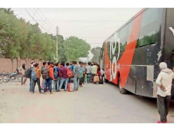 लाॅकडाउन की घाेषणा हाेने के बाद प्रवासी श्रमिक अपने घर वापस जाने के लिए निकले। सेक्टर-29 पार्ट टू स्थित ट्रैवल्स एजेंसी की बस में लाइन लगाकर चढ़ते हुए। - Dainik Bhaskar